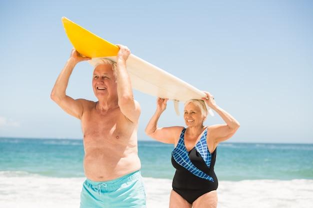 Coppia senior portando una tavola da surf
