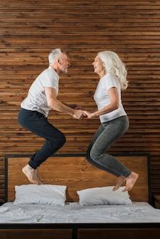Coppia senior saltando nel letto