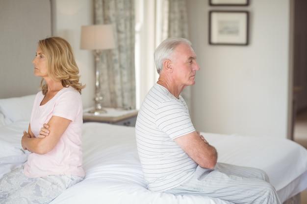 Coppia senior sconvolta seduta schiena contro schiena sul letto