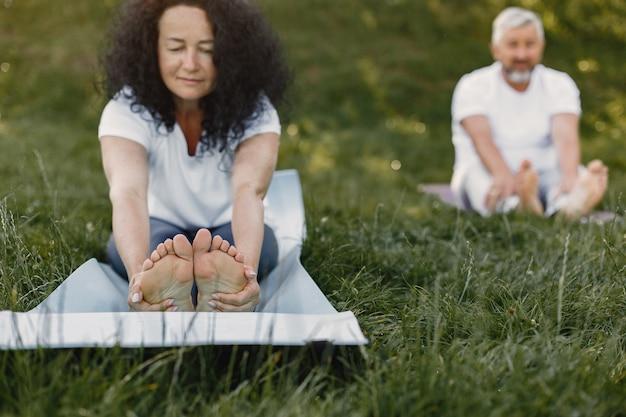 Coppia senior sta facendo yoga all'aperto. allungando nel parco durante l'alba. bruna in una maglietta bianca.