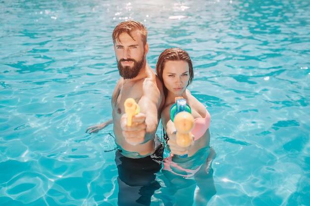 Coppia seria e concentrata si trova schiena contro schiena in piscina e guarda. pongono. ragazzo e ragazza tiene le pistole ad acqua in mano e li allunga alla telecamera.