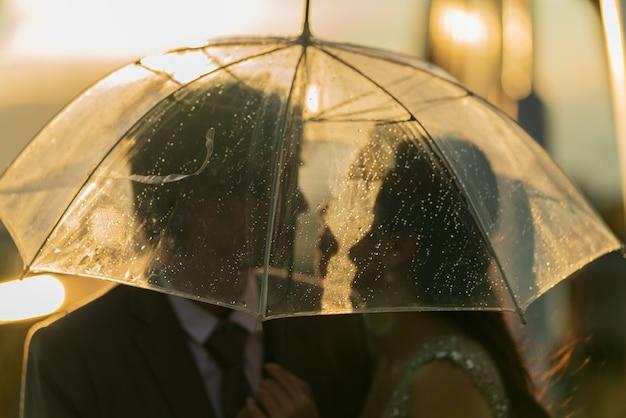 Coppia silhouette prewedding sotto l'ombrello
