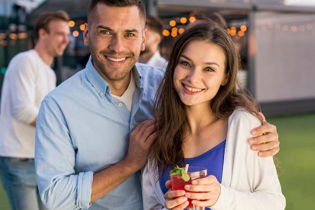 Coppia sorridente a una festa in terrazza