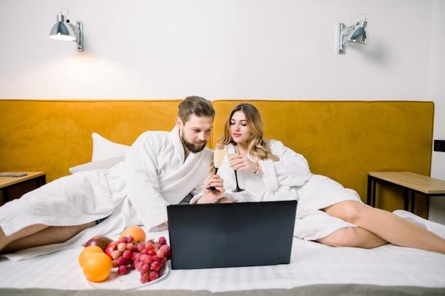 Coppia sorridente con bicchieri di champagne a letto, usando il portatile. coppia l'alcool bevente che si siede sul letto in hotel