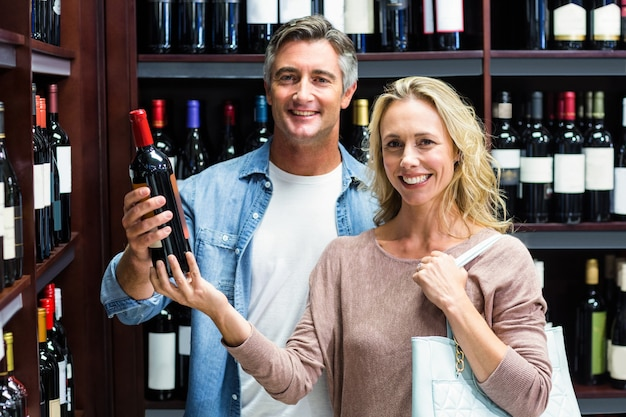 Coppia sorridente con bottiglia di vino