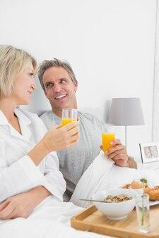 Coppia sorridente con succo d'arancia a colazione a letto
