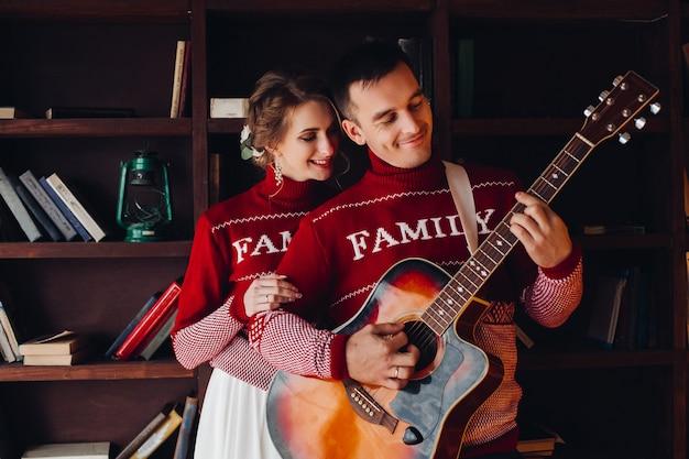 Coppia sorridente in maglioni rossi ascoltando musica