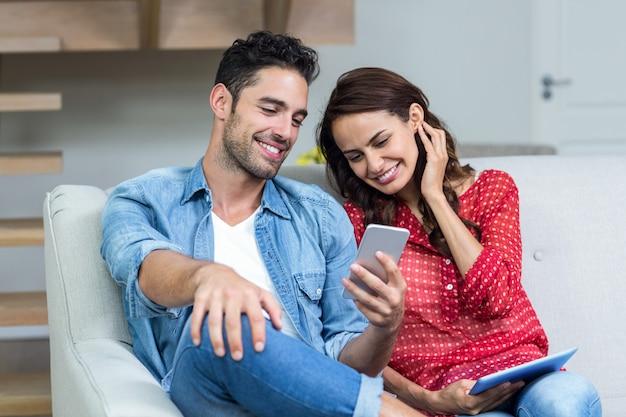 Coppia sorridente utilizzando il telefono