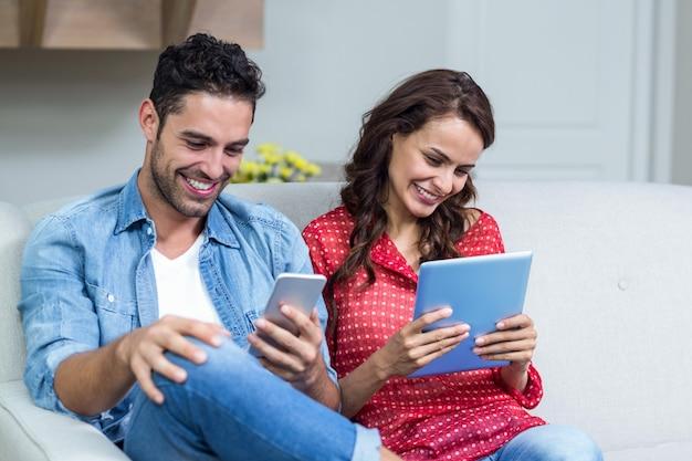 Coppia sorridente utilizzando la tecnologia