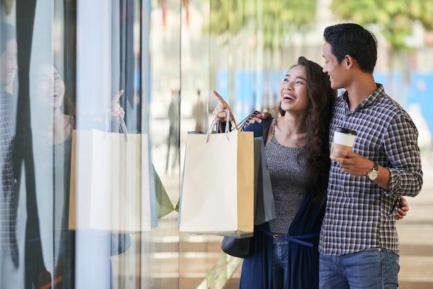 Coppia spensierata shopping finestra nel negozio di abbigliamento
