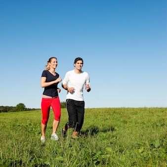 Coppia sportiva jogging a prato