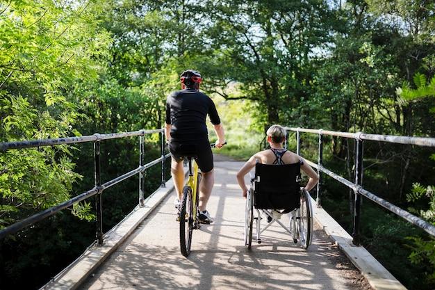 Coppia su un esercizio insieme su una bicicletta e in una sedia a rotelle