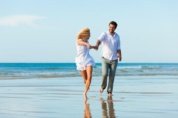 Coppia sulla spiaggia che corre nel futuro glorioso