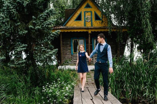 Coppia tenere le mani va su un ponte di legno vicino a una vecchia casa in legno