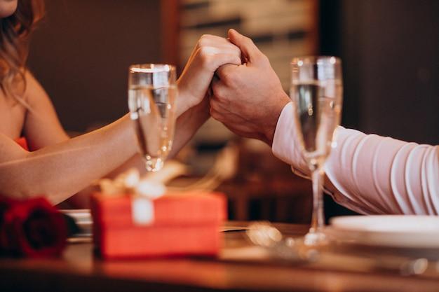 Coppia tenersi per mano sui biglietti di s. valentino che uguagliano in un ristorante