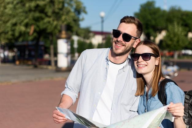 Coppia turistica carina con occhiali da sole e mappa