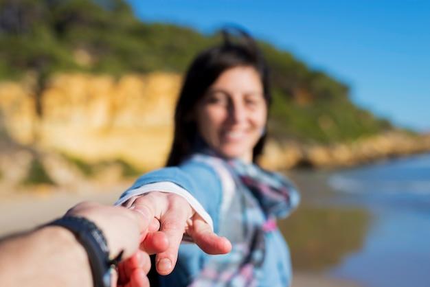 Coppia turistica divertirsi con la donna prendendo l'uomo per mano e tirando verso il mare