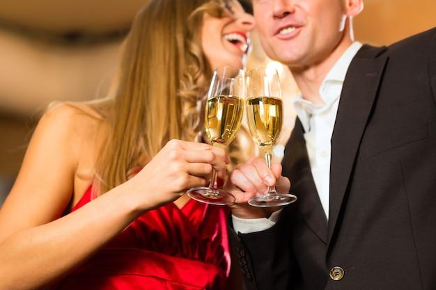 Coppia, uomo e donna, bevendo champagne in un raffinato ristorante, ognuno con un bicchiere di spumante in mano