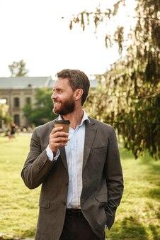Coppia uomo gioioso in abito grigio e camicia bianca, guardando a parte, mentre beve caffè da asporto durante la passeggiata nel parco verde sulla giornata di sole