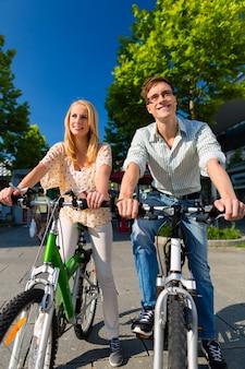 Coppia urbana in sella a bici nel tempo libero in città