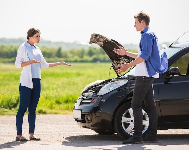 Coppia vestita casual avendo litigio vicino a un'auto rotta.