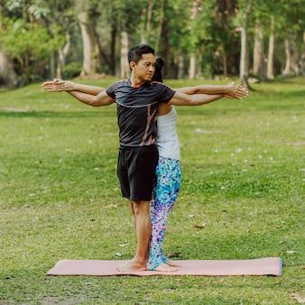 Coppia, yoga, erba e alberi