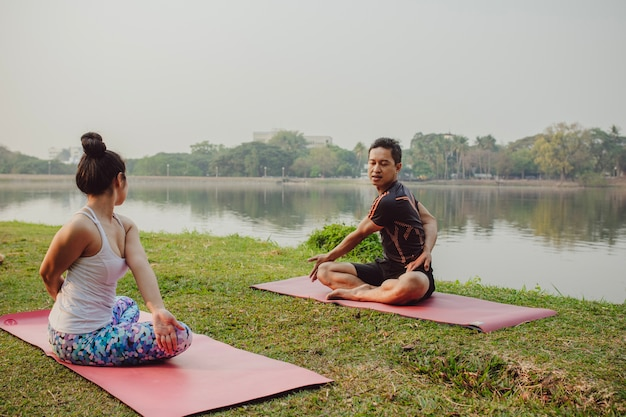 Coppia, yoga, lago e natura