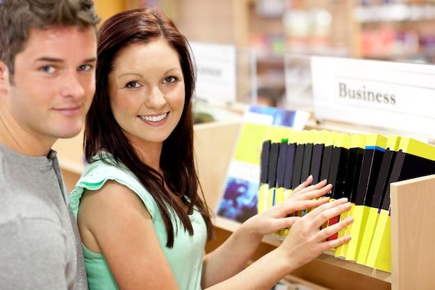 Coppie adorabili che cercano un libro di affari in una biblioteca