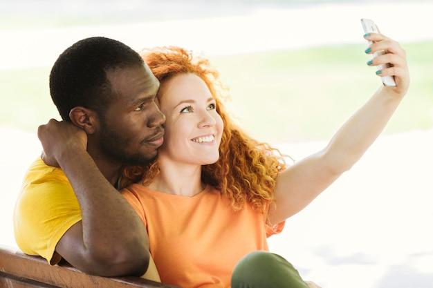 Coppie adorabili che prendono un selfie nel parco