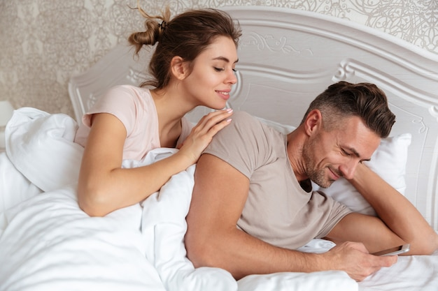 Coppie adorabili sorridenti che si trovano insieme a letto