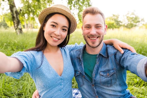 Coppie adulte multirazziali felici che prendono selfie al parco