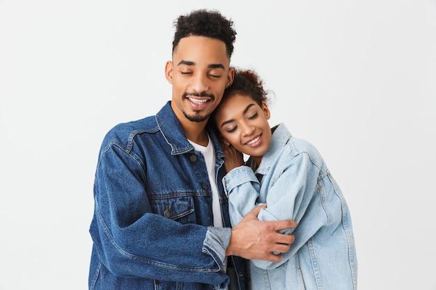 Coppie africane adorabili felici in camice del denim che abbracciano insieme agli occhi chiusi sopra la parete grigia