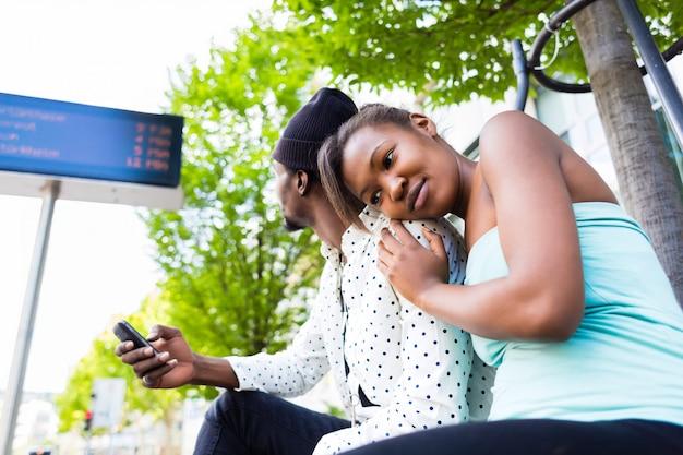 Coppie africane che aspettano all'autostazione