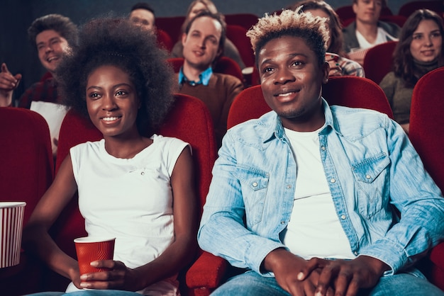 Coppie africane con popcorn guardando film nel cinema
