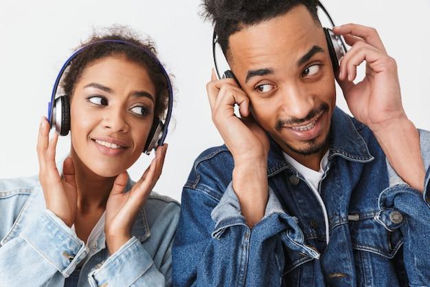 Coppie africane piacevoli nella musica d'ascolto delle camice del denim dalle cuffie mentre guardandosi l'un l'altro sopra la parete grigia