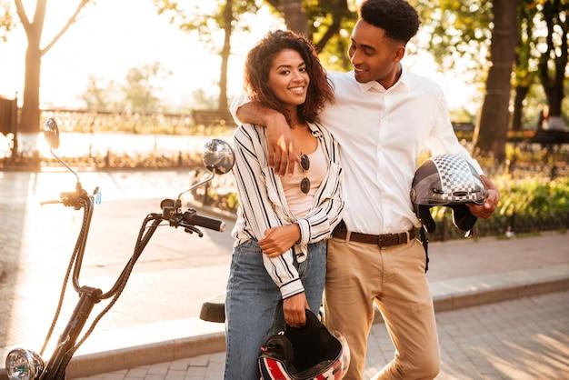 Coppie africane spensierate che abbracciano vicino alla motocicletta moderna nel parco