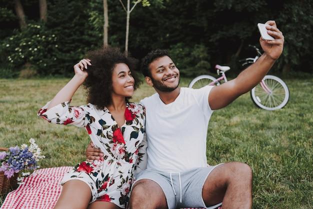 Coppie afroamericane che fanno selfie in legno