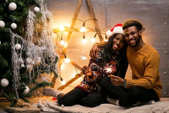 Coppie afroamericane che si siedono con le luci di bengala dall'albero di natale