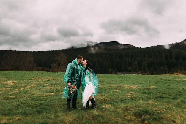 Coppie alla moda che camminano e baciano nella natura
