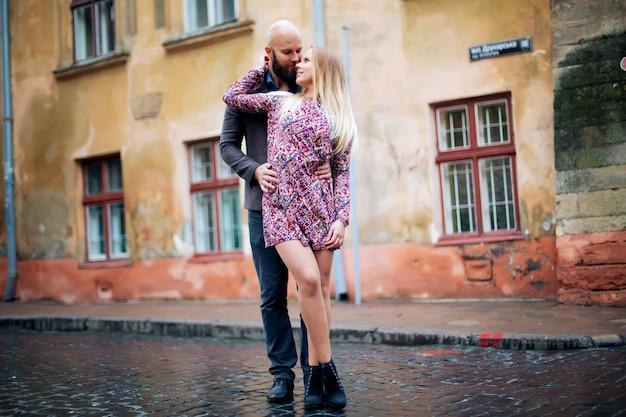 Coppie alla moda eleganti di giovane modo che posano sulle vie della città europea nel tempo di sera di estate. ragazza bionda sensuale di moda con divertiresi bello dell'uomo dei pantaloni a vita bassa all'aperto.