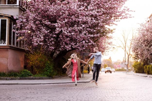 Coppie alla moda nel parco con l'albero di sakura con i fiori rosa di fioritura. bella giovane coppia, uomo con barba e donna bionda che si diverte nel parco primavera.