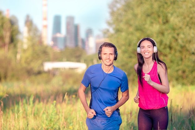 Coppie allegre attive che corrono nel parco. salute e fitness.