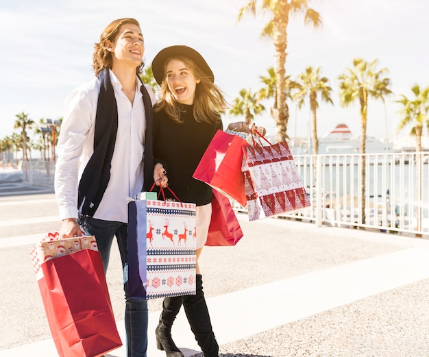 Coppie allegre che camminano con i sacchetti della spesa di natale