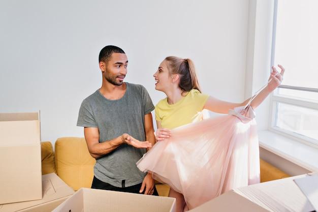 Coppie allegre che disimballano le scatole, la famiglia si è trasferita in una nuova casa, ha acquistato un appartamento. vestiti unboxing della giovane donna, che tengono la gonna rosa. moglie e marito in camera, con indosso maglietta, top giallo, pantaloncini.
