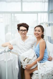 Coppie allegre che fanno lavanderia automatica