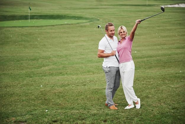 Coppie allegre che giocano a golf su un campo da golf, stanno alla buca successiva