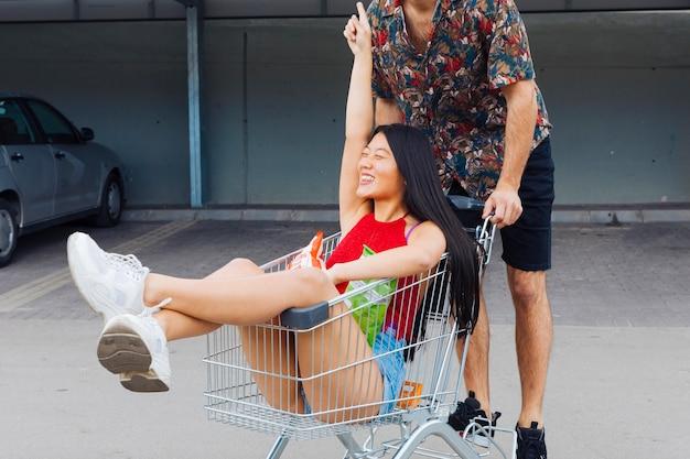 Coppie allegre che guidano nel carrello di acquisto