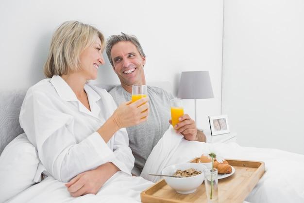 Coppie allegre che mangiano succo d'arancia a colazione a letto
