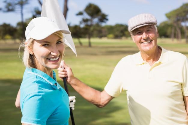 Coppie allegre del giocatore di golf che tengono bandiera bianca