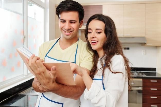 Coppie allegre in grembiuli che leggono il libro di cucina